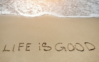 life is good written on the sand beach - positive thinking concept